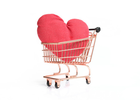 Side view of shopping cart with big red heart isolated on white background