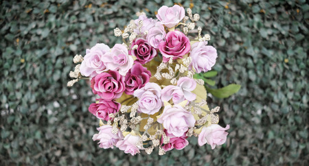 Top of beautiful artificial bouquet of gradient flowers on green leaves Imagens