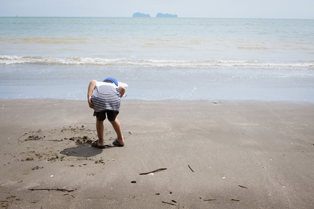 Behind of boy searching for hermit crab and garbage collector hobby and leisure concept