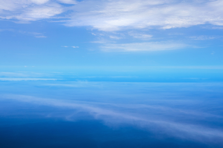 Aerial view with cloud ripples above the ocean and fluffy cloudscape