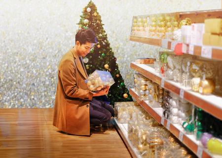 Man enjoy choosing Christmas decoration in the shop Imagens