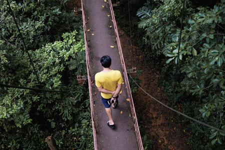 Man walking on canopy walkway in (Thung khai) botanic garden