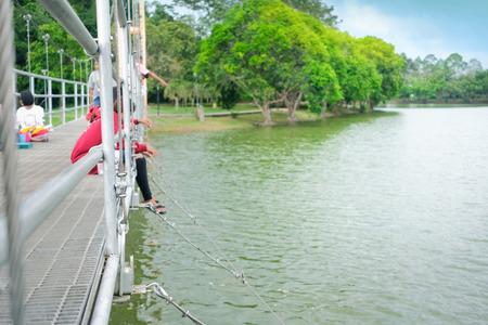 People enjoy feeding fish on suspension bridge. Selective focus