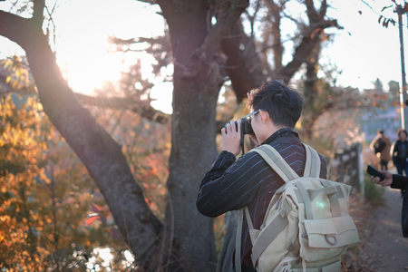 Backpack man taking pictures in autumn season Imagens - 123867004