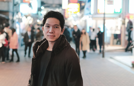 Attractive young man on walking street in Shibuya, Tokyo Japan