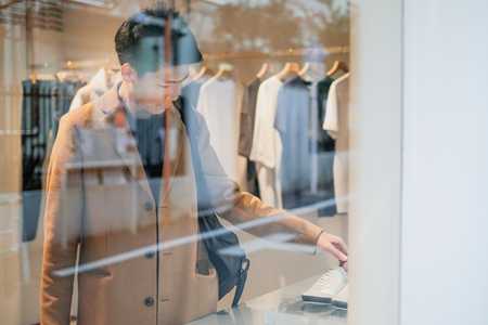 Young man shopping in the clothes shop. Looking through the window Imagens - 123868932