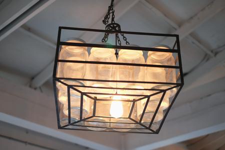 Hanging a dozen of bottles lamp on vintage ceiling Imagens