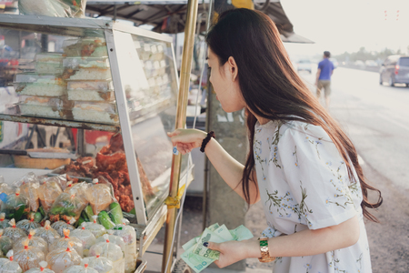 Beautiful girl choosing foods at the street market in Thailand Imagens