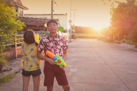 Boy and girl play water gun together on Songkran festival in Thailand over sunset scene background