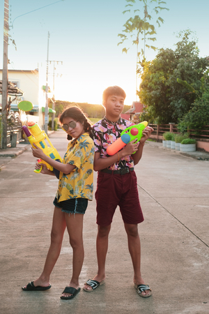 Boy and girl play water gun together on Songkran festival in Thai Imagens