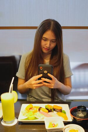 Young beautiful girl use smartphone and taking food picture before having japanese meal Imagens - 127788338