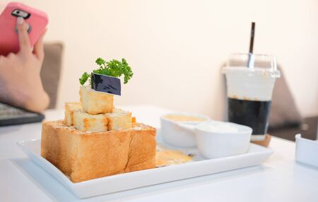 Girl take honey toast picture with salted egg sauce and ice-cream before eat. Set of dessert foods and drink at the cafe Imagens - 127788340
