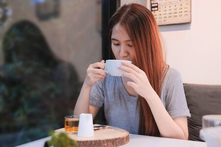 Beautiful girl drinking tea in the coffee shop and restaurant