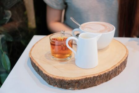 Set of hot drink on wooden tray on dining table Imagens - 127788345