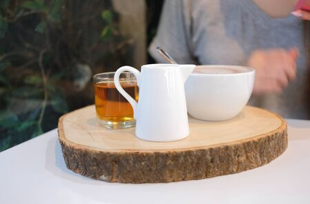 Set of hot drink on wooden tray on dining table Imagens