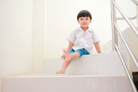 Playful schoolboy sitting on the stair Imagens - 127788479