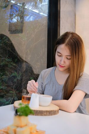 Young attractive girl holding spoon and stirring hot coffee in domestic life