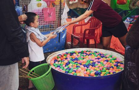 Little boy received the prize from winning fishing and scooping colourful eggs game