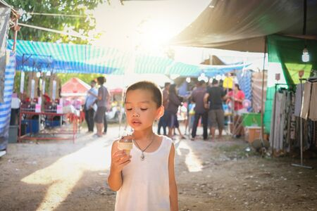 Little boy enjoy eating chocolate ice-cream cone while walking in the market