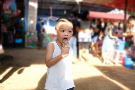 Small kid enjoy eating chocolate ice-cream cone while travel in the market on sunny day. Isolated and clipping path