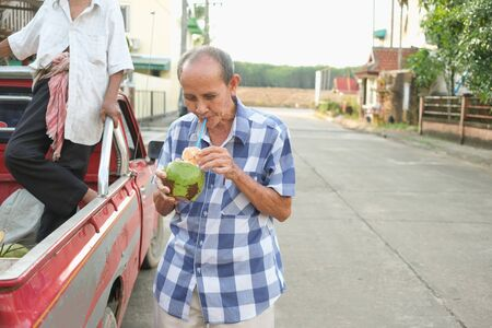 Old man drinking fresh coconut juice after buy and take a break Banco de Imagens