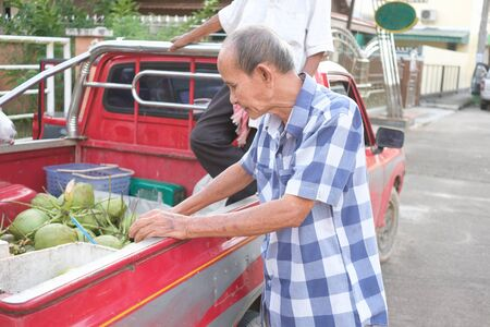 Old man choosing and buying coconuts on pickup truck Imagens - 131598652