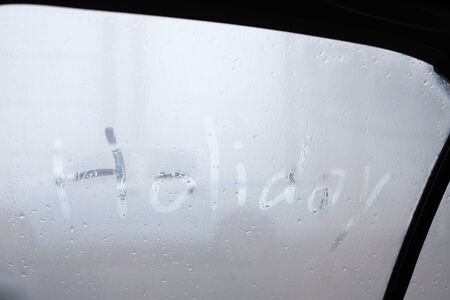 Travel on raining day in holiday with finger draw word on cars window