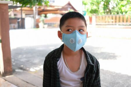 Boy wear purely anti-pollution air mask when go outside to protect corona virus ( covid-19 ) and pm 2.5 dust