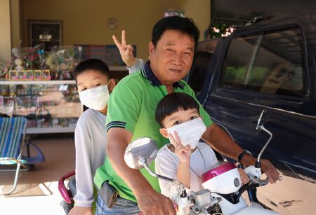 Grandfather took two grandsons go to market and wear white masks protection