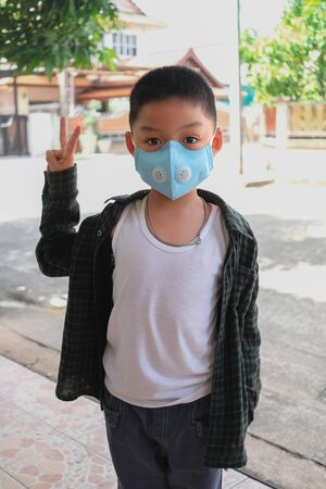 Boy raise two fingers to fighting for corona virus ( covid-19 ) and wear blue mask