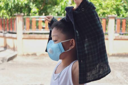 Little boy wearing jacket and blue mask to go outside the house in Corona virus ( Covid-19 ) epidemic period
