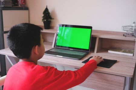 Asian boy stay at home while surfing the internet on laptop