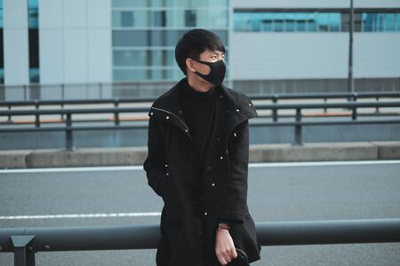 Portrait of young man wear black mask and black coat in big city