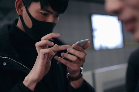 Young man using smartphone while waiting for subway