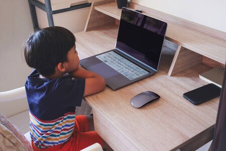 Young boy stay at home while enjoy watching something on laptop Banco de Imagens