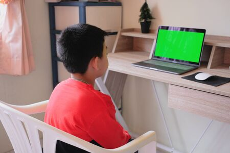Asian boy stay at home while watching something on laptop Banco de Imagens