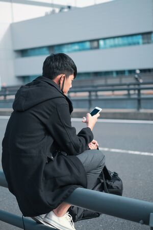 Young asian man sitting on road barrier waiting for bus and taxi driver concept while using smart phone