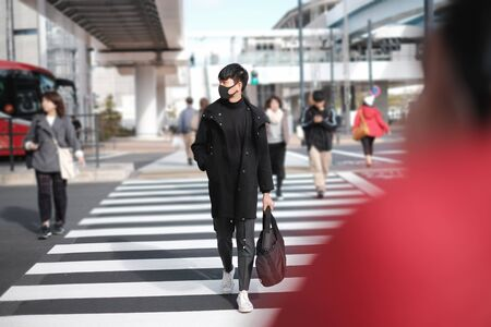 Young asian man wearing black surgical mask and carrying bag crossing road to other side in big city and photo shooting model concept
