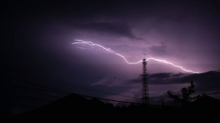 Real lightning bolt striked on the top of antenna tower in Trang Thailand at night Banco de Imagens