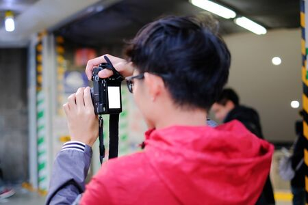 Rear view of young photographer taking a shot on the street in Tokyo, Japan. Selective focus Banco de Imagens