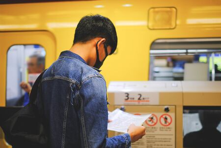 Young man wear protective face mask while open the map and searching the places to travel by subway from rear view