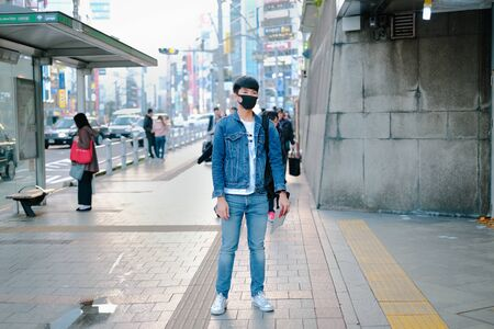 Young man standing in street wearing denim and waiting for bus to travel and japanese language on roof is bus stop, Ueno park destination Banco de Imagens