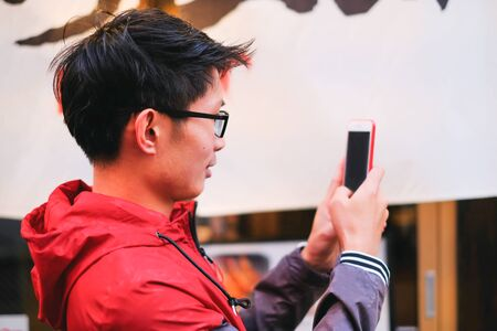Side view of young asian man unlocking smartphone with facial recognition and touching fingerprint while using phone for video call and chatting with friend concept