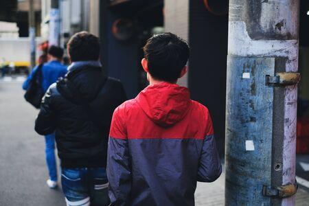 Young men walking on city street in Tokyo, Japan