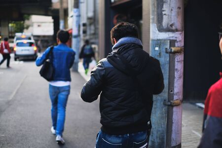 Man walking on the street while using smart phone and social distancing concept from behind