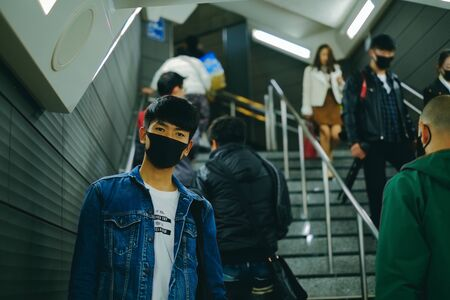 Man wear protective face mask in subway station with other people to protect virus. Covid-19 protection concept when go outside at public place Stock Photo