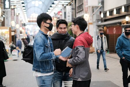Group of young asian friends talking about the trip to travel on walking street while open the map Banco de Imagens
