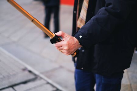Close up man holding selfie stick for taking self-portrait while traveling