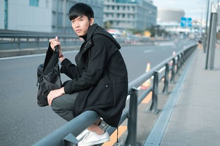 Handsome young asian man carry bag to travel while sitting on metal fence on footpath