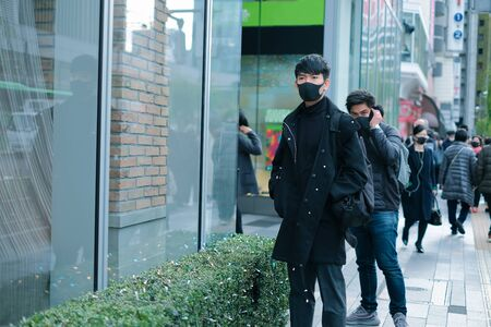 Lifestyle of young men wear protective face mask in big city and corona virus spreading period concept Banco de Imagens